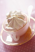 Meringue in rosa Tasse mit Untertasse und Gabel