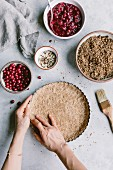 A woman is prepping the dough for a cranberry almond tart