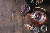 Stillleben mit verschiedenen Teesorten in Gläsern und Teekanne mit aufgebrühtem Tee