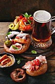 Fried sausages, wienerwurst, ham, marinated chili peppers in salted pretzels with basil and glass of lager beer