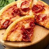 Pizzastücke mit Mozzarella, Schinken und Basilikum
