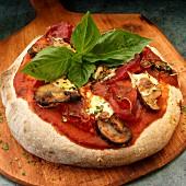 Ganze Vollkorn Pizza mit Schinken, Pilzen, Mozzarella und Basilikum auf Pizzaschieber