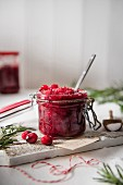 Homemade cranberry sauce in a storage jar