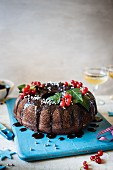 Chocolate bundt cake with chocolate sauce and red currants