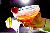 Womans hand holding a strawberry bellini cocktail in a bar