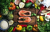 Raw uncooked salmon steak with vegetables, rice, herbs, spices and wine bottle on chopping board