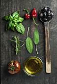 Greek black olives, fresh green sage, rosemary, basil herbs, oil, tomato, peppers on wooden background