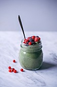 Matcha green tea chia pudding topped with frozen berries in a glass jar