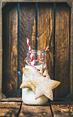 Bottle with milk and Christmas festive gingerbread star shaped cookies with decoration rope on wooden background