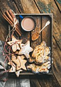 Cocoa in mug with Christmas gingerbread star shaped cookies and pieces of Stollen cake in wooden tray