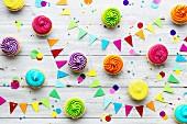Verschiedene bunte Party-Cupcakes mit Partydeko auf Holzuntergrund