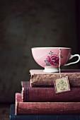 Vintage-Teetasse mit Blumenmotiv auf Stapel alter Bücher