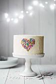 weiße Festtagstorte mit Herz aus bunten Zuckerstreuseln auf Tortenständer