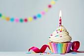 Geburtstags-Cupcake mit brennender Kerze und bunten Zuckerstreuseln