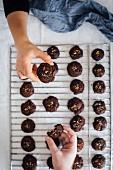 Hände greifen fertiggebackene Schokoladen-Zitrusplätzchen