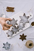 A hand is grabbing one of the snowflake cookies served on a white marbled board