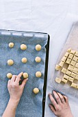 Hands placing cookie balls in a baking pan