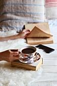 Frau mit Buch und einer Tasse Kaffee auf Bett