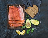Smoked salmon filet with lemon, avocado, fresh herbs and bred on wooden serving board over dark stone backdrop