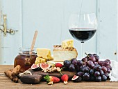 Glass of red wine, cheese board, grapes, fig, strawberries, honey and bread sticks on rustic wooden table
