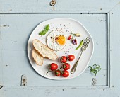 Breakfast set. Fried egg, bread slices, cherry tomatoes, hot peppers and herbs on white ceramic plate