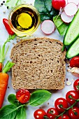 Slice of a whole wheat bread and healthy organic vegetables for making sandwiches