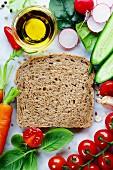 Zutaten für gesunde Sandwiches: Vollkornbrot umgeben von Biogemüse