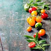 Verschiedene orange, rote und grüne Tomaten auf Holzuntergrund