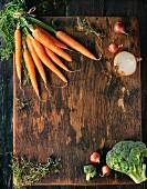 Gesunde Lebensmittel: Karotten, Zwiebeln, Brokkoli und Thymian auf Holzbrett