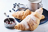 Two fresh baked croissants with sugar powder served with jam, aluminum cup of milk