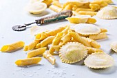 Homemade ravioli and garganelli pasta with flour and wooden roller over light blue wooden background
