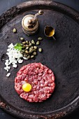 Beef tartar with capers and fresh onions on black textured background