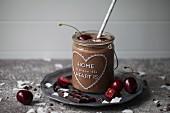 Schokoladen-Kokossmoothie im Glas dekoriert mit Kirsche, Schokolade, Kokosflocken und Kakaonibs