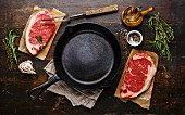 Raw fresh meat Steak Striploin for two with ingredients around frying pan