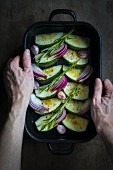 Hands holding an oven dish with courgette, onions and fresh herbs prepared for cooking