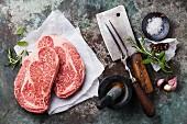 Rohe marmorierte Black Angus Steaks mit Gewürzen und Küchenutensilien