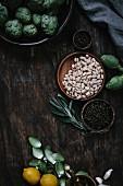 Zutatenstilleben: weiße Bohnen, Kapern, Zitronen und Mini-Artischocken