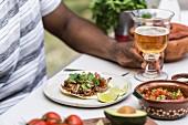 Dunkelhäutiger Mann mit Rindfleisch-Taco und Bier an Tisch im Freien