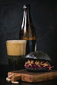 Black homemade burger with stews and red cabbage served on chopping board with glass and bottle of dark beer