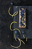 Square Lemon tartlet with fresh blueberries, served on black stone slate with lemon zest over black background