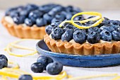Close up of Two Lemon tartlets with fresh blueberries, served on blue ceramic plate