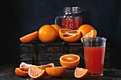 Sliced and whole Sicilian Blood oranges and glass of fresh red orange juice over old wooden table