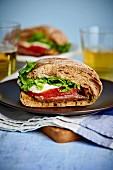 Sandwich mit Schinken, Tomate, Mozzarella und Salat