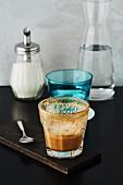 Halb leergetrunkener Kaffee, Wasserglas, Zuckerstreuer und Wasserkaraffe auf Restauranttisch