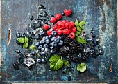 Mix of fresh berries with ice on blue wooden background