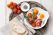 Frühstück mit Spiegeleiern, Tomaten und Speck