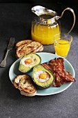 Breakfast with eggs baked in avocado, bacon, bread toast and orange juice