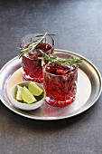 Two glasses of Cranberry cocktail with rosemary garnish