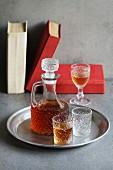 Stillleben mit Likör in Karaffe und Gläsern, im Hintergrund Bücher