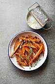 Sweet potato fries in an enamel plate with grated parmesan, spices and thyme